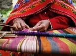woman weaving colorful fabric by hand