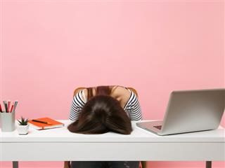 woman with head down on desk in frustration