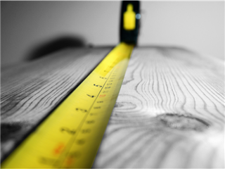 A tape measure stretched across a piece of lumber - measuring success concept