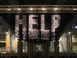 shimmery help sign hanging from front of building