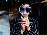 person with big magnifying glass in front of their eyes