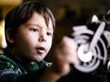 child looking in wonder at the wheel of a toy motorcycle