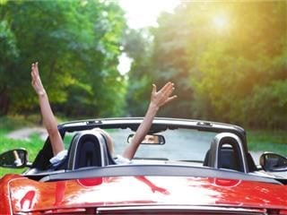 A convertible car being driven hands-free by a woman - driving higher education's CMS needs concept