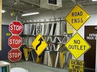 "A bunch of street signs, including three ""Stop"" signs, a ""Road Ends"" sign and a ""No Outlet"" sign."