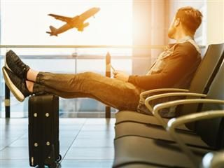 man sitting on a chair in an airport lounge with feet on luggage watching a plane take off