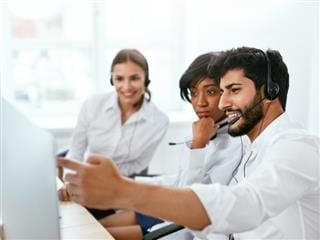 Three contact center agents looking at a computer screen.