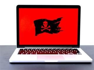 image of a laptop with a pirate flag on a red screen