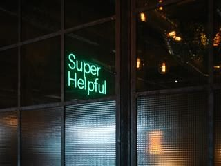 "a peek into a commercial space with lit neon sign reading ""Super Helpful"""