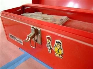 red toolbox with magnets of Fred Flintstone and Barney Rubble on it.