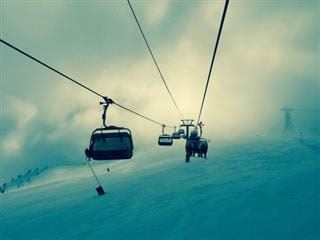 skiers in a ski lift, separated by compartment