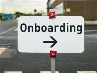 "An sign that says ""Onboarding"" with arrow to the right side. In an outdoor setting - employee onboarding concept"