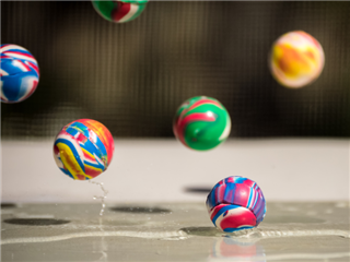 A bunch of high bounce balls bouncing off a wet countertop - Bounce Rate Concept