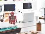 red robot next to a laptop on a desk