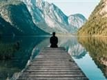 Person sitting at end of a dock overlooking a river between mountains.