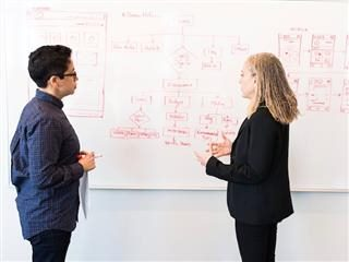 two colleagues having a business discussion  in front of a whiteboard