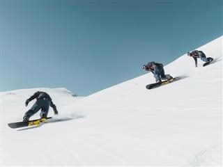 3 snowboarders accelerating downhill