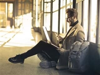 A businessman traveling, while checking his company's intranet to find a necessary contract for an upcoming meeting.