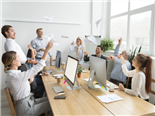 Multiracial corporate team of young and senior business people launching paper planes together in office, diverse motivated employees group laughing having fun at work