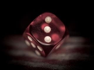 red die with the side with three dots showing