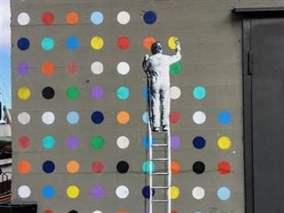 street art of a person standing on a ladder, painting a series of dots on a wall