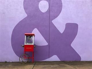 Ampersand painted on a wall with a popcorn machine in front
