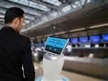 Man interacting with chatbot kiosk at airport