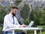 A businessman sitting at a desk working at his computer, situated in an out door environment with a mountainous background - Officeless workplace concept