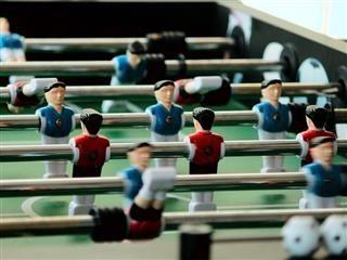 close up of foosball figures, opposing teams
