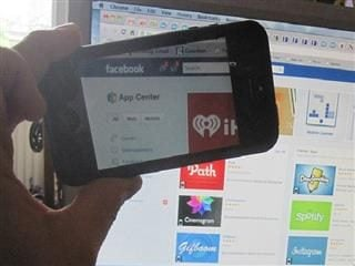 Someone holding a smart phone up to a computer screen taking a picture of a page with Facebook apps.