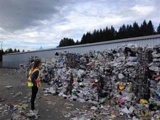 woman surveying compacted trash