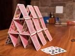 house of cards on a wood table, connoting instability