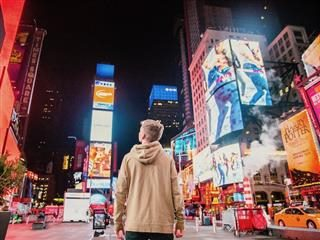 back of a person standing in the middle of Times Square in NYC, looking up  at all the advertisements