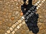 A cobblestone street with a double white line and a person's shadow crossing the line - cross the line concept