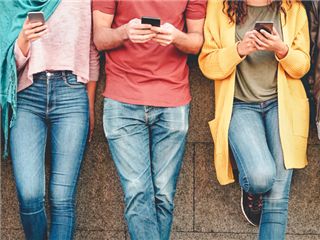 A group of friends, outdoors, leaning against a wall while using their smart mobile smartphones.