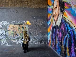 man with tuba next to Shakespeare mural