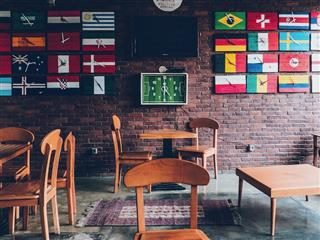 empty cafe with wall covered in clocks made from flags around the world