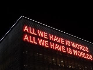"neon sign reading: ""All We Have Is Words // All We Have Is Worlds"""