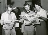 three people holding newspapers, two men and a woman, one of the men is smoking a cigar.
