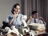 '50s scenario, woman calculating and on phone, man in background smoking a pipe