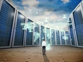 Rear view of businessman with hands in pockets in a big data center
