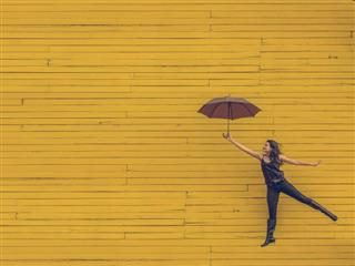 woman holding umbrella leaping in front of a yellow wall