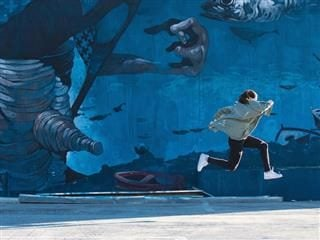 high leap in front of a mural