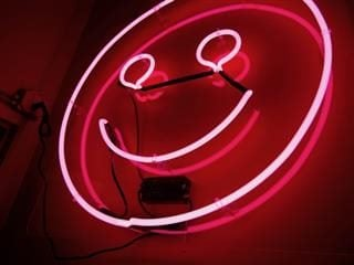 pink neon emoji smiley face sign