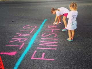 two young girls mark the start and finish lines of a race using bright pink spray paint