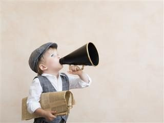 young boy shouting into a megaphone while he holds a newspaper.