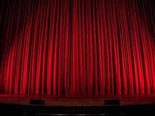 red curtain lit up on empty stage