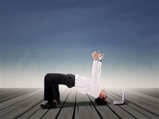 Happy businessman doing bridge yoga over PC with blue sky background