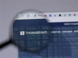 """magnifying glass hovers over the words """"thomabravo"""" on a computer screen."""