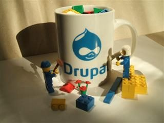 A coffee mug with Drupal written on it along with Drupal logo, surrounded by Legos.