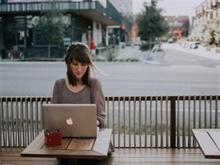 woman working on laptop in outdoor cafe